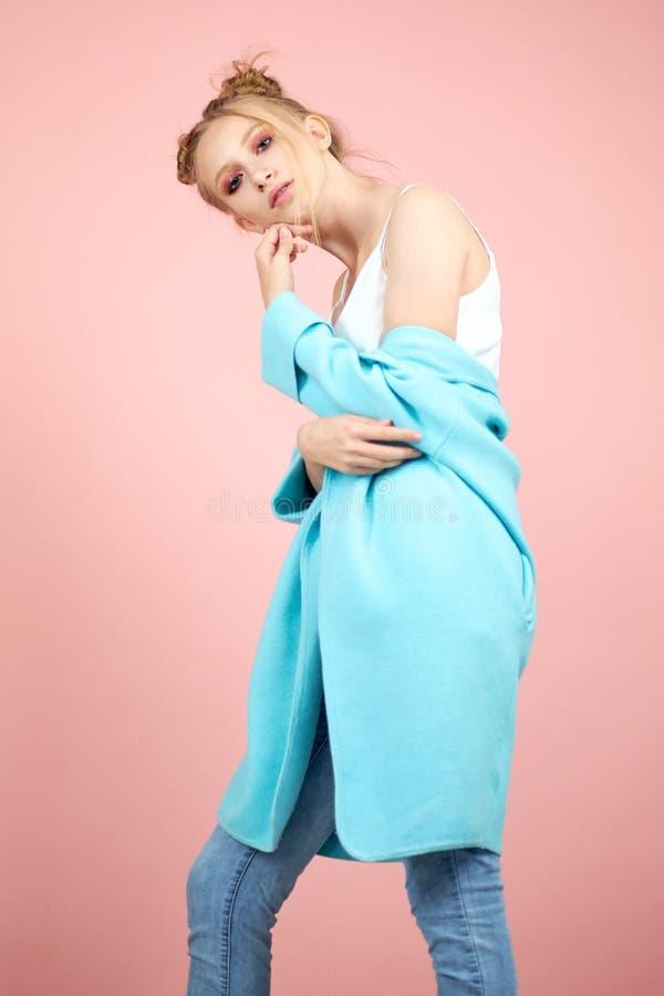 Glückliches Modell des jungen Mädchens, das im Frühjahr im Studio auf Kleidung eines rosa Hintergrundes aufwirft Mode für Teenage stockfotos