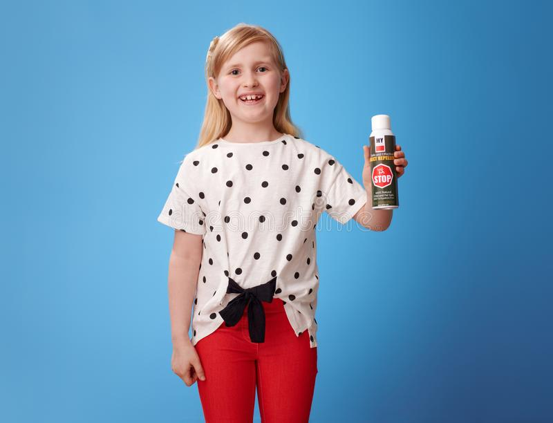 Glückliches modernes Kind in den roten Hosen auf blauem darstellendem Insektenvertilgungsmittel stockfoto