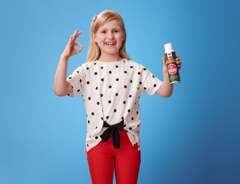 Glückliches modernes Mädchen, das Insektenvertilgungsmittel und okaygeste auf Blau zeigt stockbild