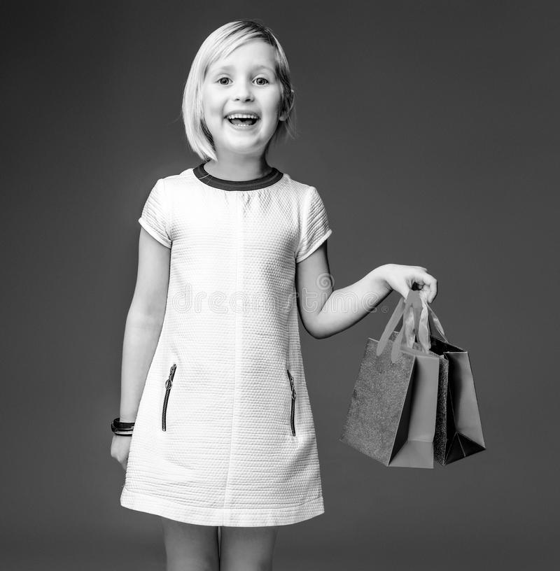 Glückliches modernes Mädchen im weißen Kleid auf dem Grau, das Einkaufstaschen zeigt lizenzfreie stockbilder