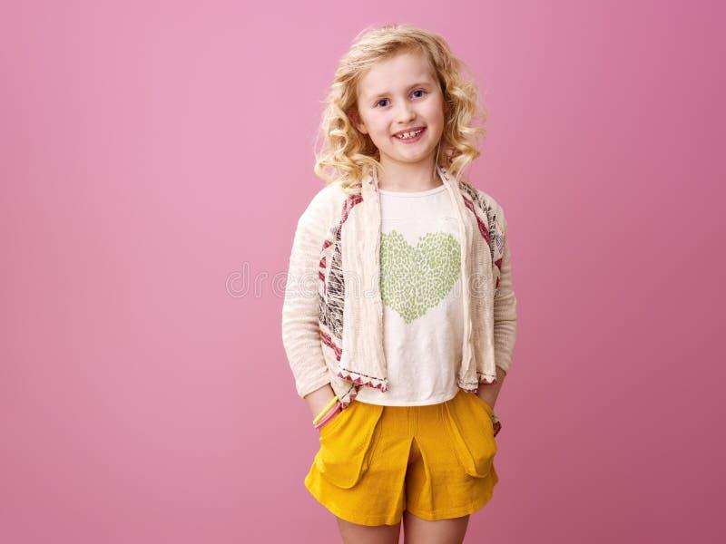 Glückliches modernes Mädchen mit dem gewellten blonden Haar lokalisiert auf Rosa stockfotos