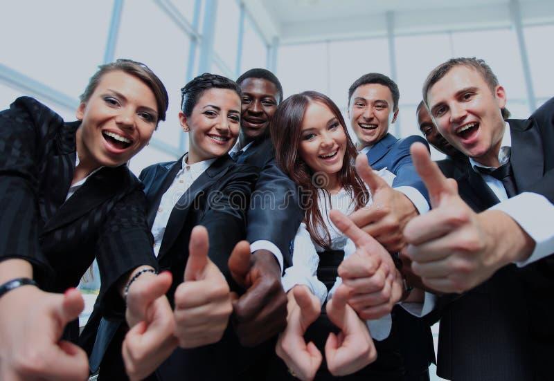 Glückliches multiethnisches Geschäftsteam mit den Daumen oben im Büro stockfoto