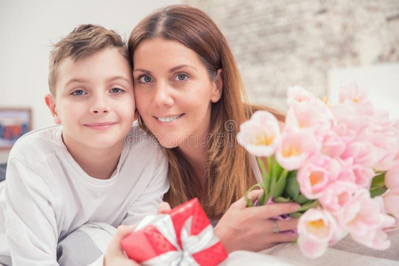 Glückliches Mutter ` s Tageskonzept Mutter mit Sohn auf Bett mit Geschenk und Tulpen stockbild