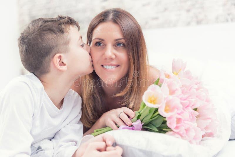 Glückliches Mutter ` s Tageskonzept Mutter mit Sohn auf Bett mit Geschenk und Tulpen Sohn küsst seine Mutter lizenzfreies stockbild