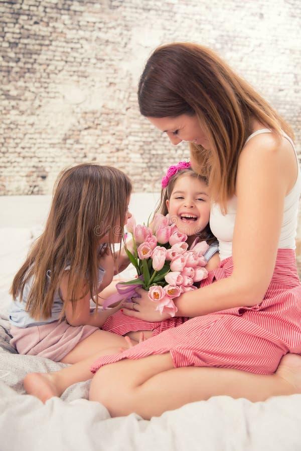 Glückliches Mutter ` s Tageskonzept Mutter mit twocute jungen Tochterzwillingen auf dem Bett im Schlafzimmer und einem Blumenstra stockfotos
