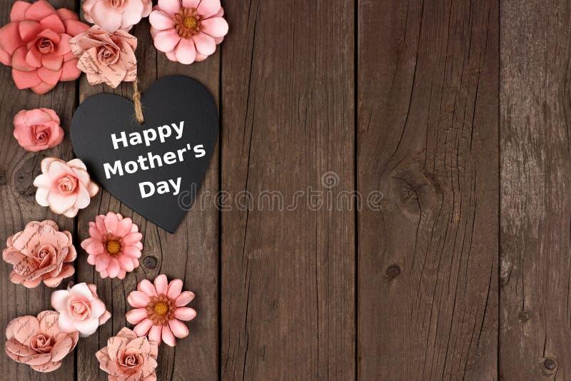 Glückliches Mutter-Tagestafelherz mit Blumenseitengrenze auf Holz stockfotos