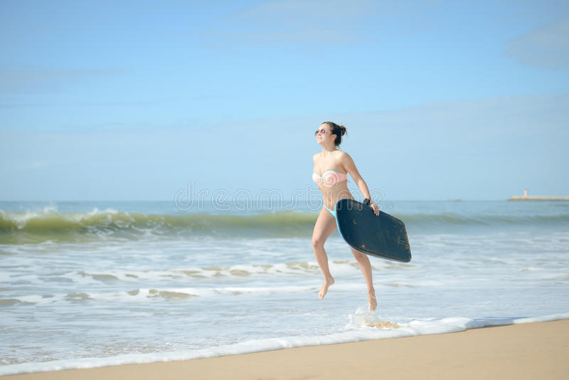Glückliches nettes gehendes Surfen des frohen Surfermädchens am Ozeanstrand, der in Wasser läuft Weibliche Bikinifrauenüberschrif lizenzfreie stockbilder