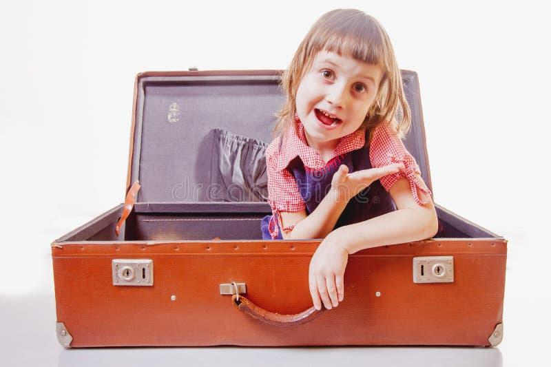 Glückliches nettes kleines Kindermädchen, das im Koffer und Wartereise und Abenteuer auf weißem Hintergrund sitzt stockbild