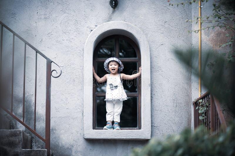 Glückliches nettes kleines Mädchen, das das Fenster lächelt und bereitsteht stockfotos