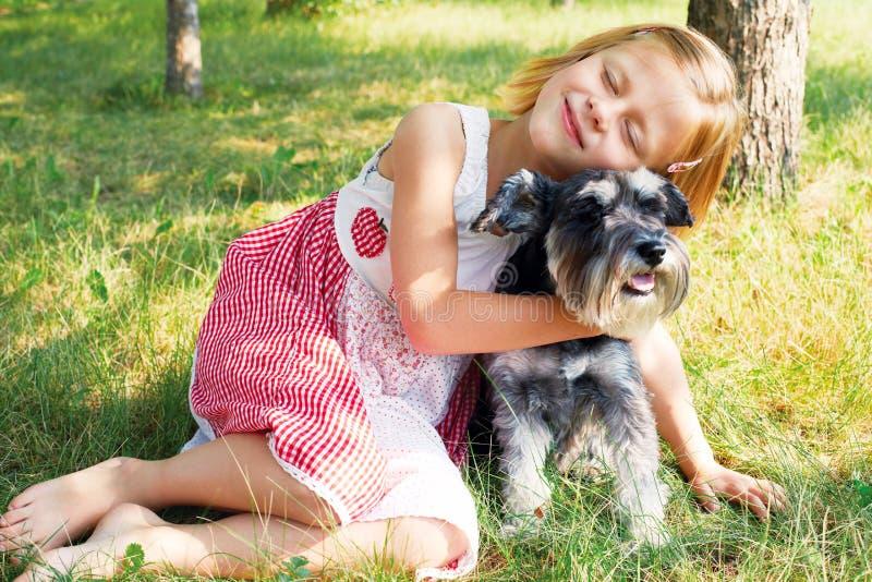 Glückliches nettes kleines Mädchen, das ihren kleinen Hund umarmt stockbild