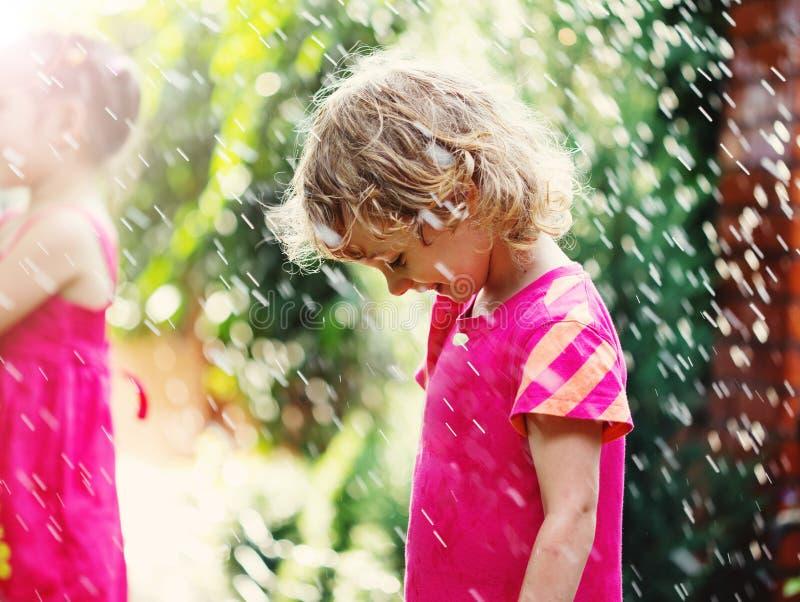 Glückliches nettes kleines Mädchen, das unter dem Regen steht lizenzfreie stockfotos