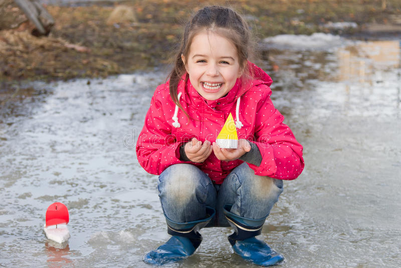 Glückliches nettes kleines Mädchen in den Regenstiefeln, die im Frühjahr mit dem Nebenfluss der Schiffe steht im Wasser spielen stockfoto