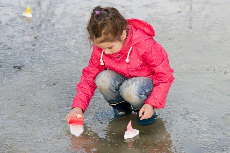 Glückliches nettes kleines Mädchen in den Regenstiefeln, die mit handgemachten bunten Schiffen wässern spielen im Frühjahr, Pfütz stockfotos