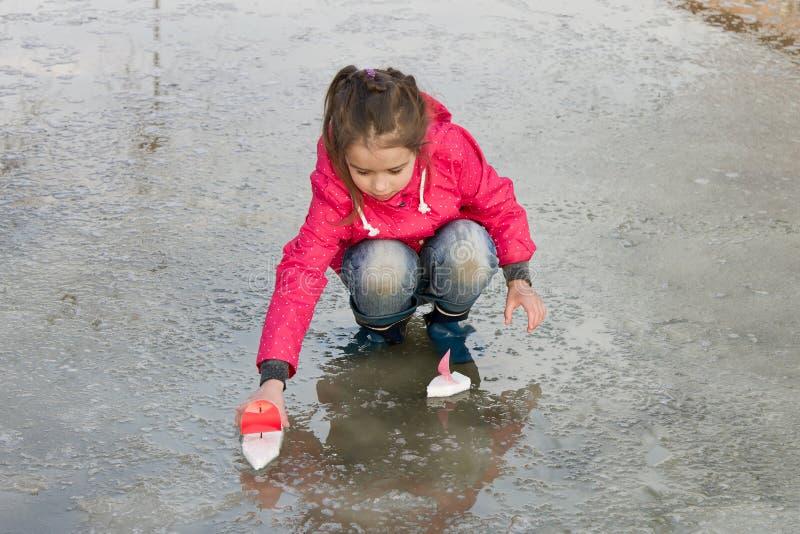 Glückliches nettes kleines Mädchen in den Regenstiefeln, die mit handgemachten Schiffen wässern spielen im Frühjahr, Pfütze stockbild