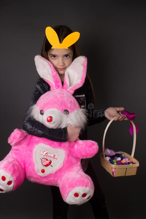 Glückliches nettes kleines Mädchen mit Ostern-Spielzeug und -ohren stockfotos