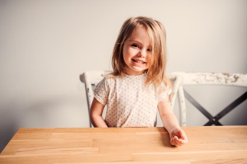 Glückliches nettes Kleinkindmädchen, das in der Küche spielt stockfotografie