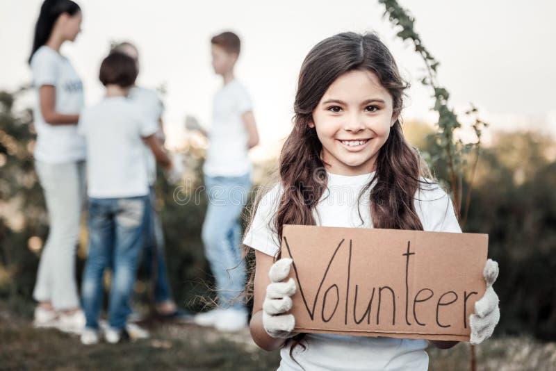Glückliches nettes Mädchen, das ein Freiwilliger ist stockfotografie