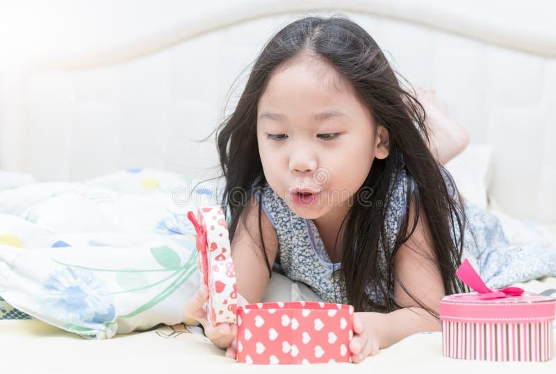 Glückliches nettes Mädchen, das eine Valentinsgruß ` s Geschenkbox öffnet lizenzfreie stockbilder