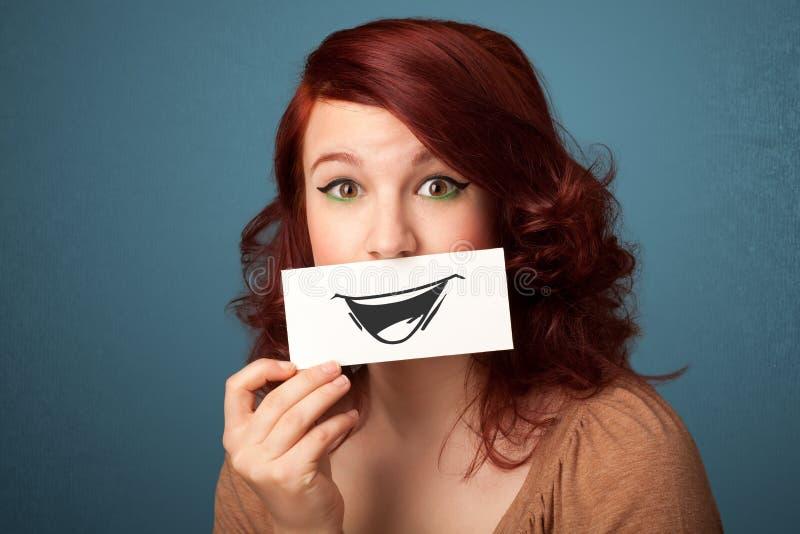 Glückliches nettes Mädchen halten Papier mit lustiger smileyzeichnung lizenzfreie stockfotos