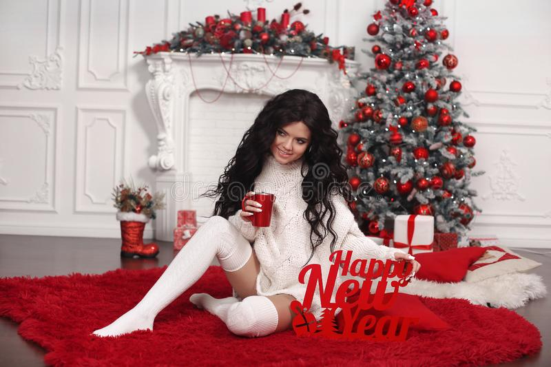 Glückliches neues Jahr Schöner Brunette in den woolen hohen Socken der Strickjacke und des Knies trinken heißen Tee über weißer r lizenzfreie stockbilder