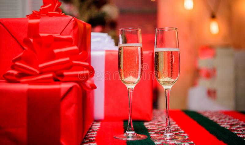 Glückliches neues Jahr und frohe Weihnachten Glas füllte Sekt oder Champagner nahe Geschenkboxen Jubelt Konzept zu Neues Jahr stockfotos