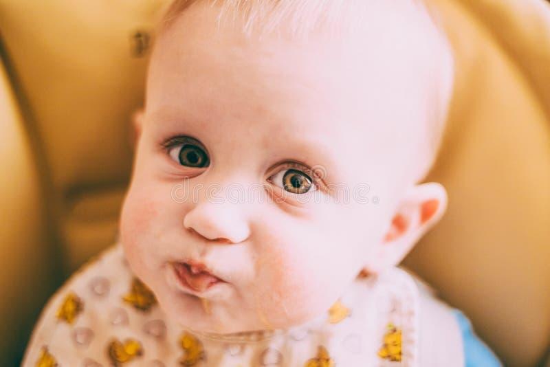 Glückliches neugieriges junges Baby, das Brei isst stockbild