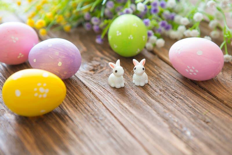 Glückliches Ostern-Konzept Ostereier mit Blumen und kleinen Häschenspielwaren auf hölzernem Brett, Ostern-Feiertagskonzept lizenzfreie stockfotos