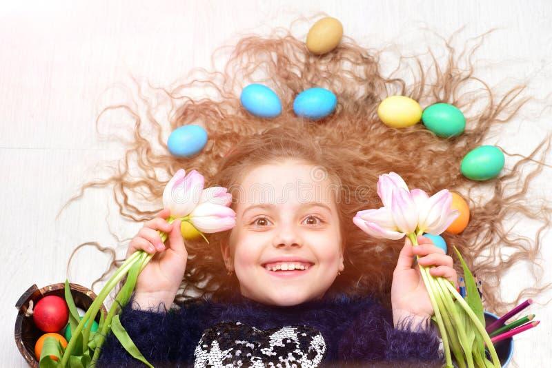 Glückliches Ostern-Mädchen, bunte Eier im langen Haar, Tulpe blüht stockfoto