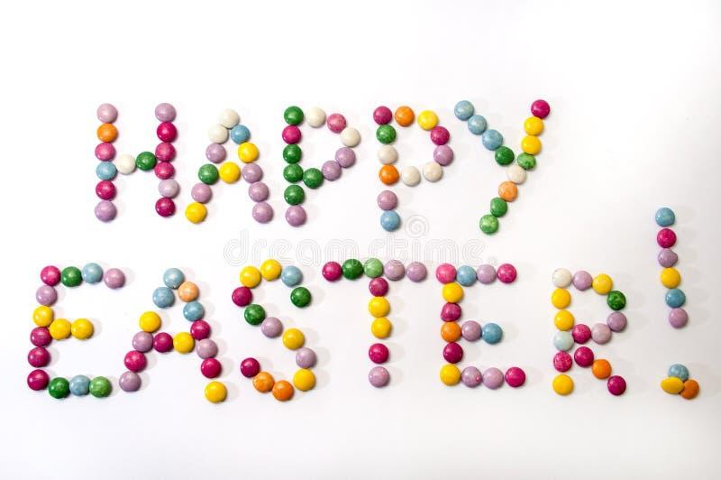 Glückliches Ostern-Zeichen der farbigen Pralinen lizenzfreie stockbilder