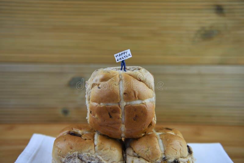 Glückliches Ostern-Zeichen hielt durch eine Miniaturpersonenfigürchen, die auf einigen frischen heißen Querbrötchen steht lizenzfreie stockfotos