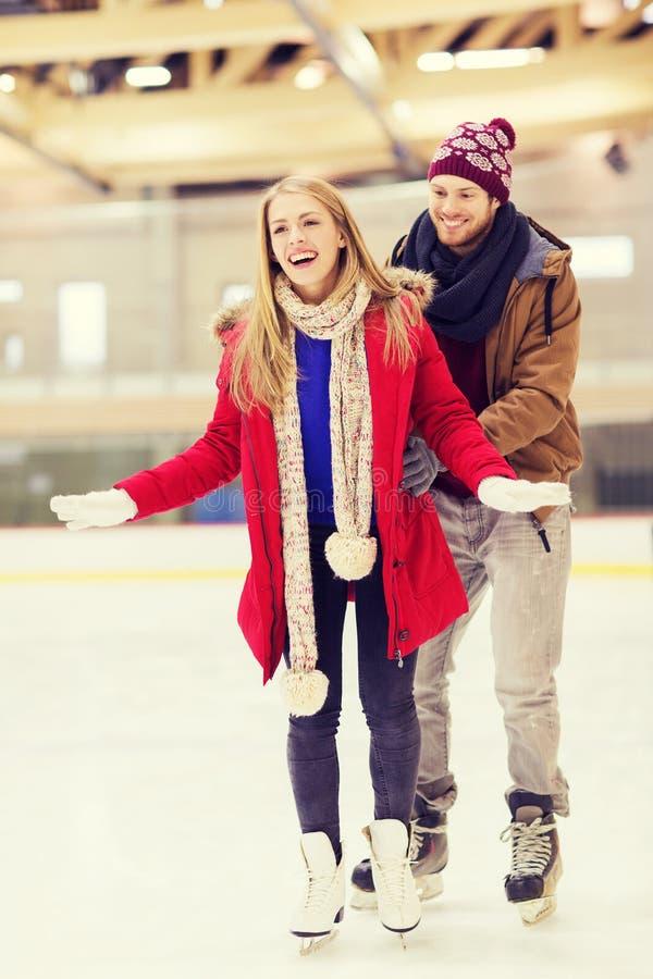 Glückliches Paar auf Eisbahn stockfotografie