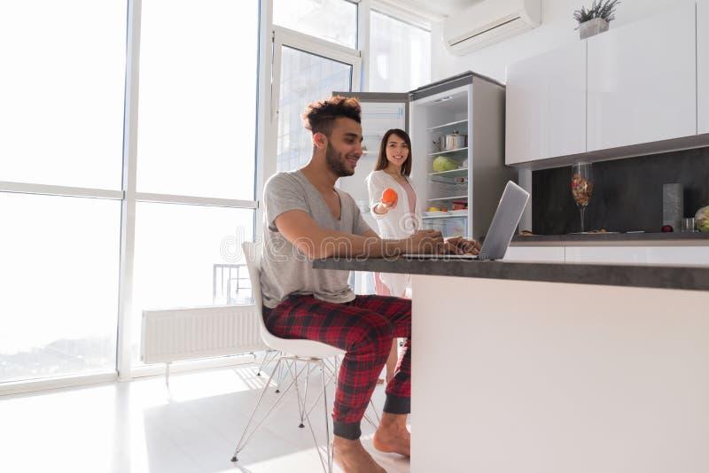 Glückliches Paar auf Küche unter Verwendung Laptop-Computer moderner Wohnung mit panoramischem Fenster stockfotos