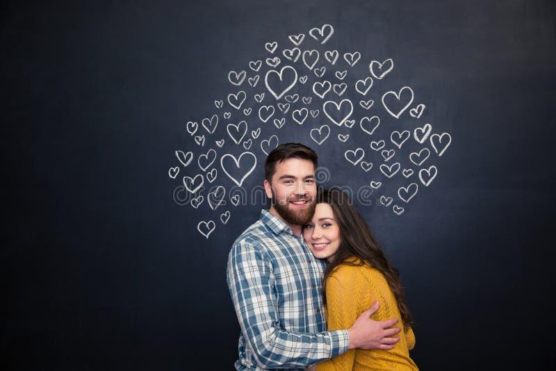 Glückliches Paar, das über schwarzem Brett umarmt und steht stockbild
