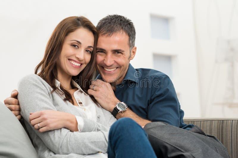 Glückliches Paar, das auf Couch sitzt stockfotografie