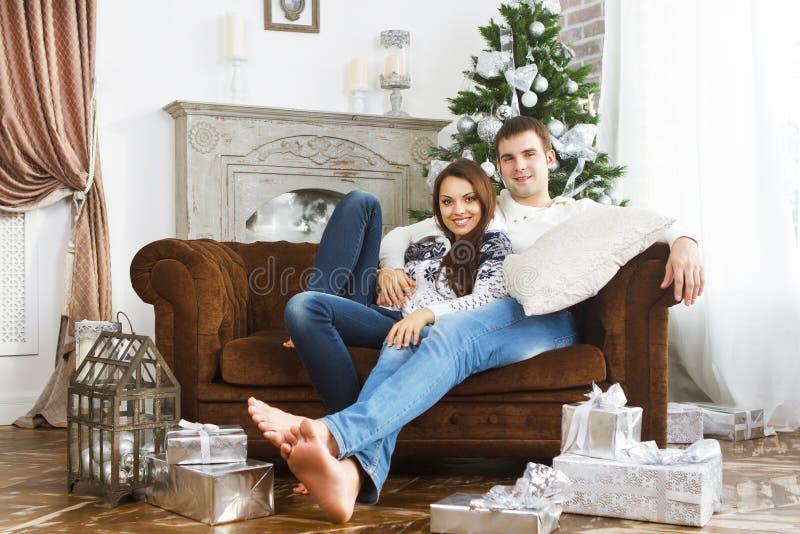 Glückliches Paar, das auf dem Sofa durch Weihnachtsbaum sitzt stockbild