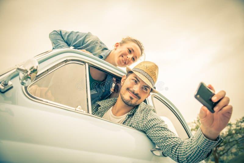 Glückliches Paar, das auf ein Weinleseauto reist lizenzfreies stockbild