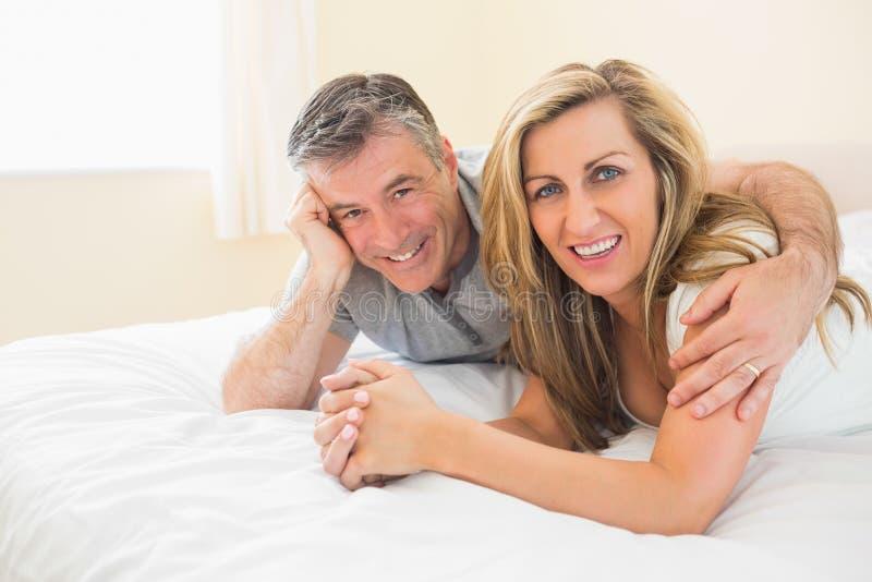Glückliches Paar, das auf einem Bett betrachtet Kamera liegt lizenzfreie stockbilder