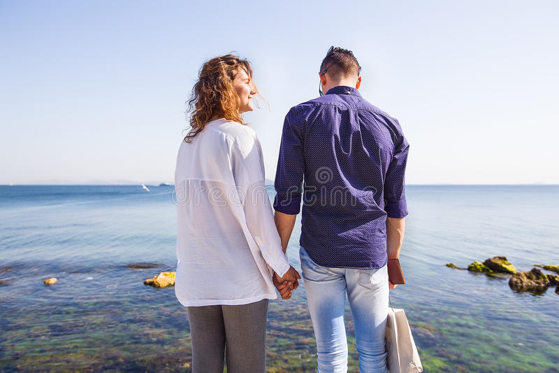 Glückliches Paar, das auf einem Seepier steht Stilvolle Paare, Hand halten, gelocktes Haar, weißes Hemd, verursachende Ausstattun stockbild