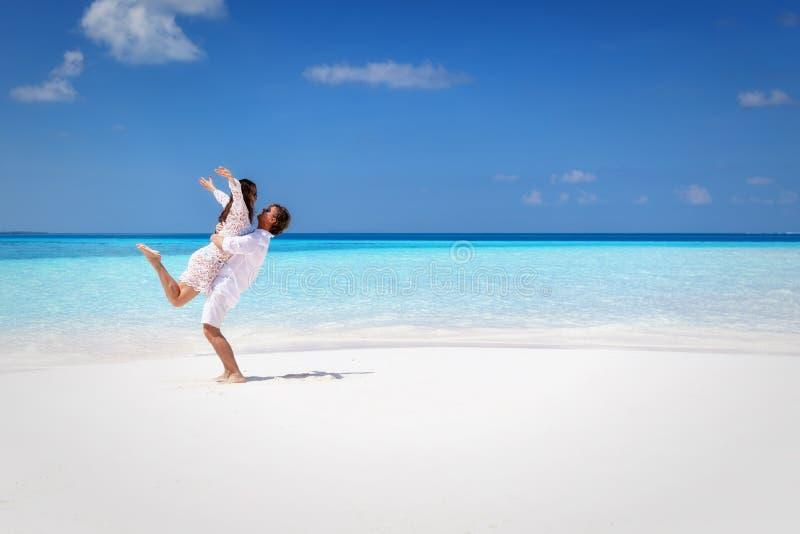 Glückliches Paar, das auf einem tropischen Strand umarmt lizenzfreies stockfoto