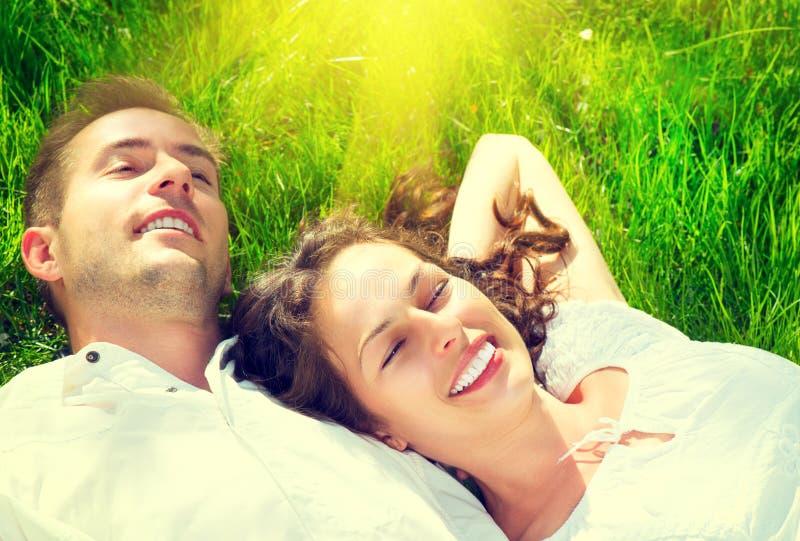 Glückliches Paar, das auf grünem Gras sich entspannt lizenzfreie stockfotos