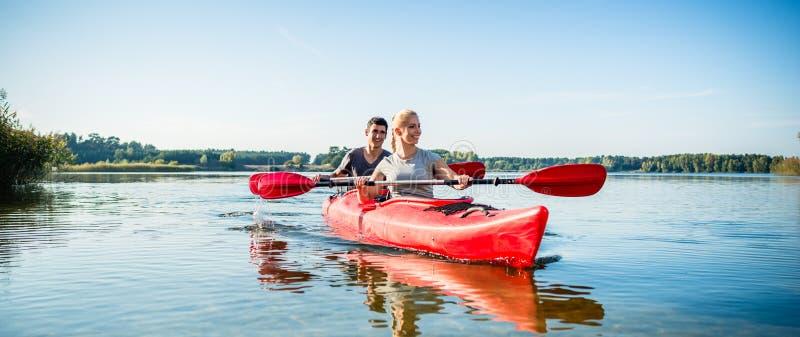 Glückliches Paar, das auf See Kayak fährt lizenzfreie stockfotografie
