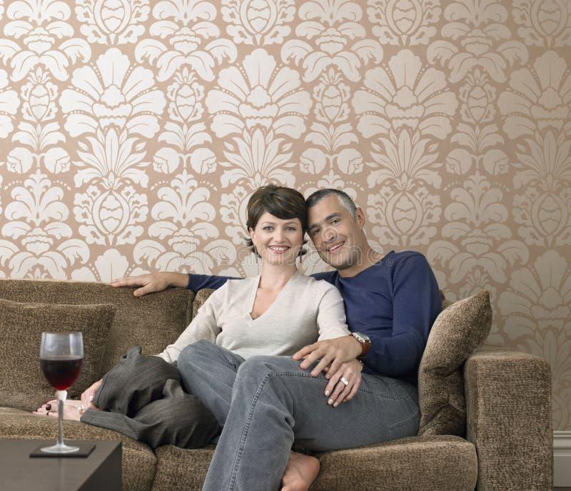 Glückliches Paar, das auf Sofa sitzt stockbild