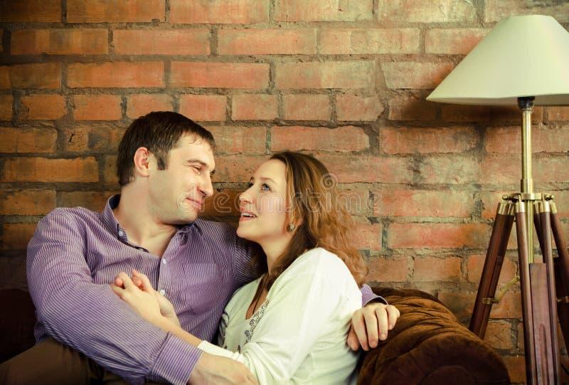 Glückliches Paar, das auf Sofa sitzt stockfotos