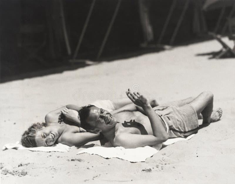 Glückliches Paar, das auf Strand ein Sonnenbad nimmt lizenzfreies stockbild