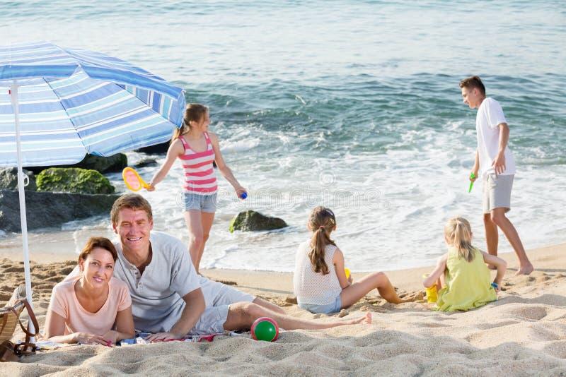 Glückliches Paar, das auf Strand mit vier Kindern stillsteht stockbild