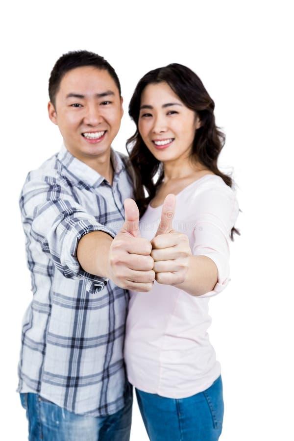 Glückliches Paar, das Daumen oben gegen weißen Hintergrund zeigt stockfotografie
