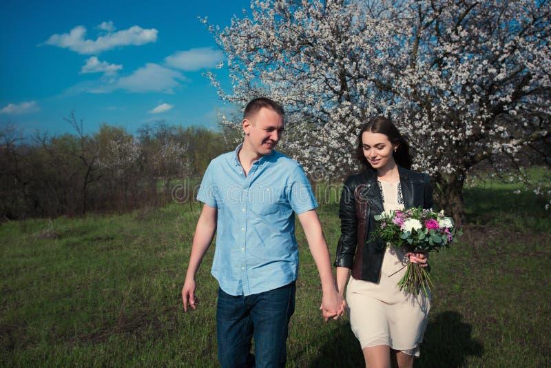 Glückliches Paar, das in den Blütengarten Hand in Hand hält läuft stockbild