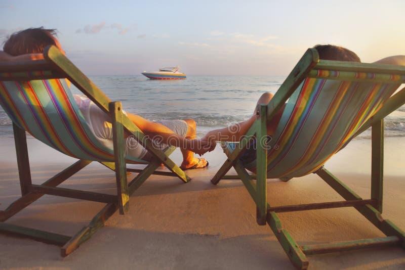 Glückliches Paar, das an den Sonnenstühlen auf dem Strand von Koh Samet an sitzt stockfoto