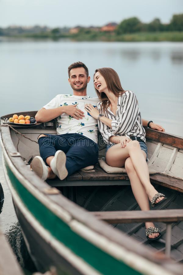 Glückliches Paar, das den Spaß sich entspannt im Boot auf See hat stockbilder