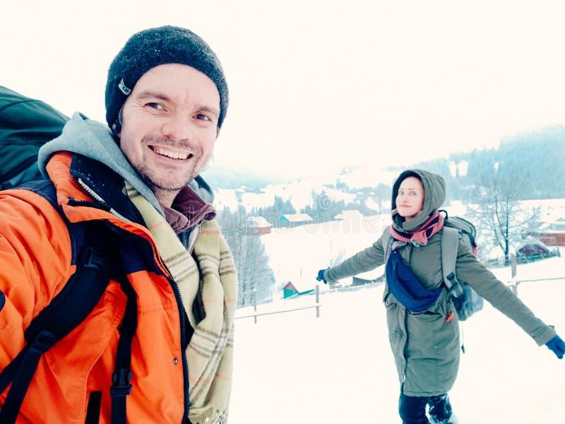 Glückliches Paar, das draußen im Winterberg lacht lizenzfreie stockfotografie